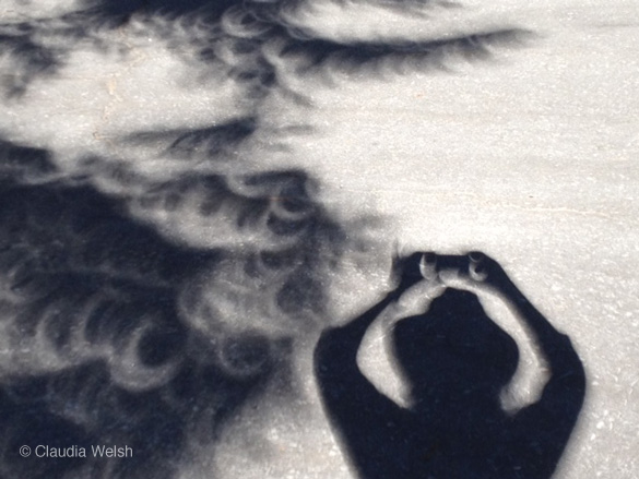 Self-portrait with crescent-shaped tree shadows during the eclipse, by Claudia Welsh