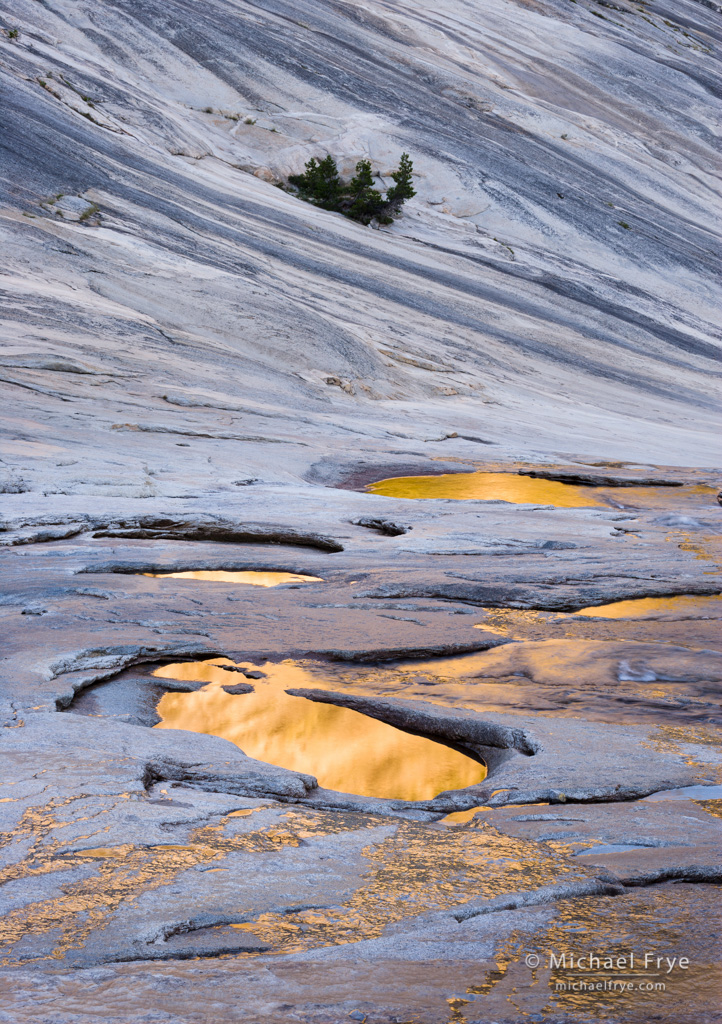 Pools in glacially polished granite, Yosemite NP. Sunlight hitting the ridge above reflected gold colors into the pools below. When setting the white balance, I left a hint of blue in the rocks to create a warm-cool color contrast.