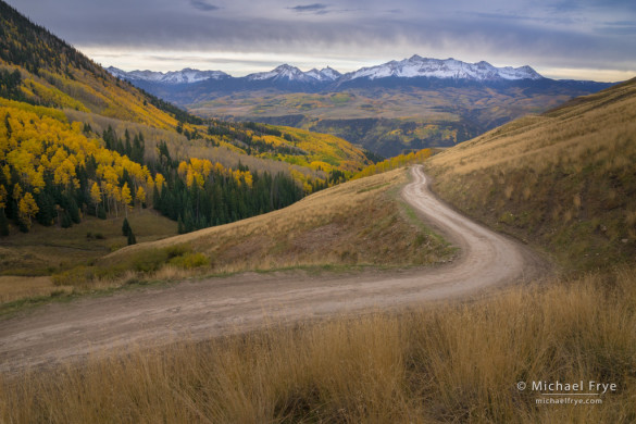 Backcountry road in autumn with the San Miguel Range in the distance, Uncompahgre NF, CO, USA